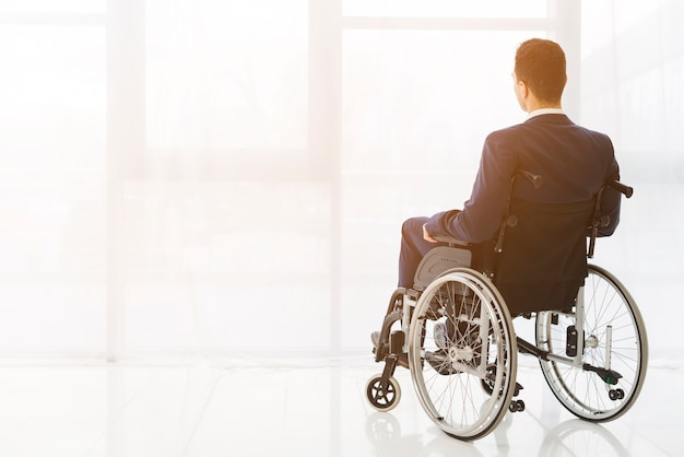 Rear view of a businessman sitting on wheelchair looking at window Free Photo
