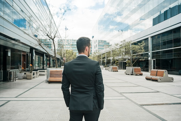 Rear view of a businessman standing on the business campus Free Photo