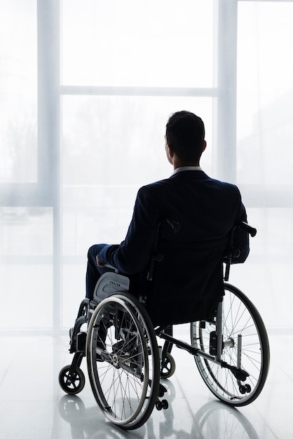 Rear view of a businessman in suit sitting on wheelchair looking at window Premium Photo