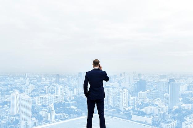 Vista posteriore di un uomo d'affari che parla al telefono in cima all'edificio Foto Gratuite
