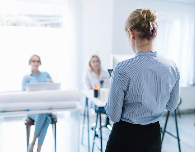 Rear view of a businesswoman giving presentation in the meeting Free Photo