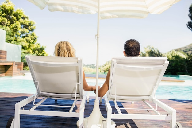Rear view of couple on deck chairs poolside Premium Photo