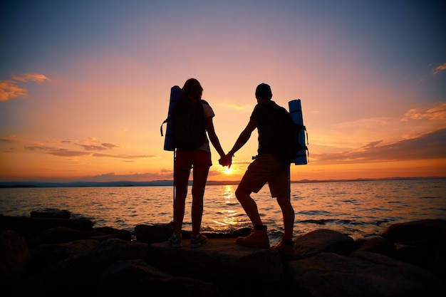Rear view of couple enjoying the sunset Free Photo