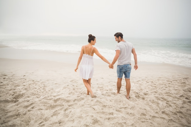 Rear view of couple holding hands and walking on the beach Premium Photo