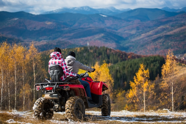 Rear view of couple on a quad bike atv at the hill Premium Photo