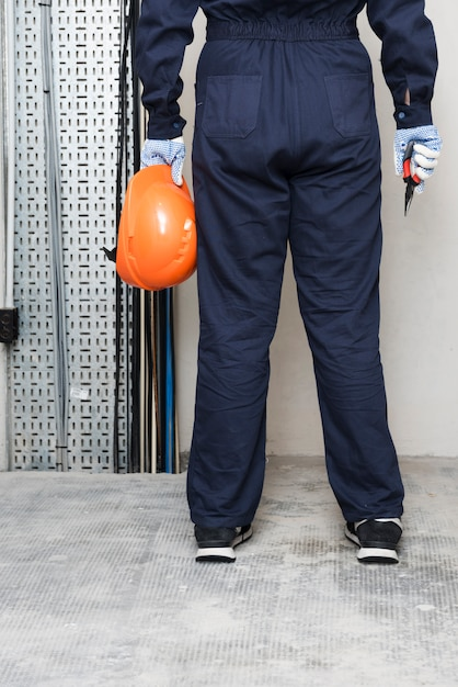 Rear view of electrician with holding hard hat and plier Free Photo