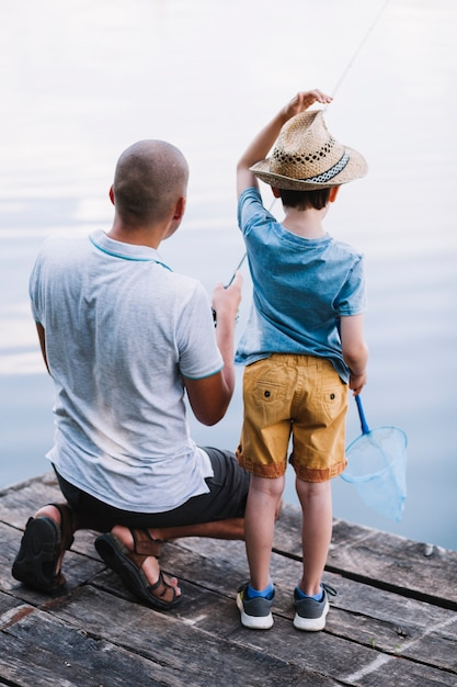 Rear view of father and boy fishing in the lake Free Photo