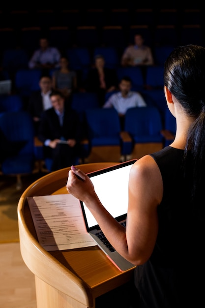 Rear view of female business executive giving a speech Free Photo