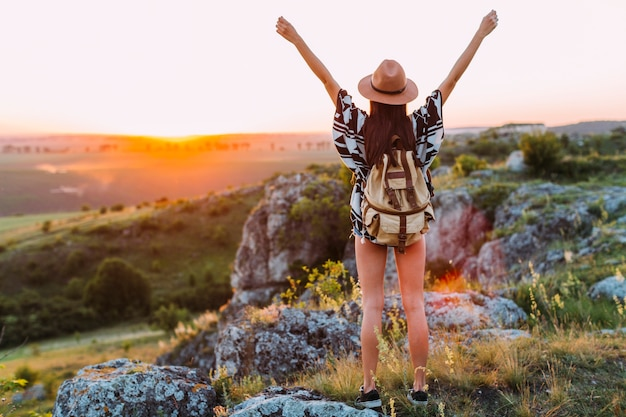 Rear view of a female hiker with arm raised Free Photo