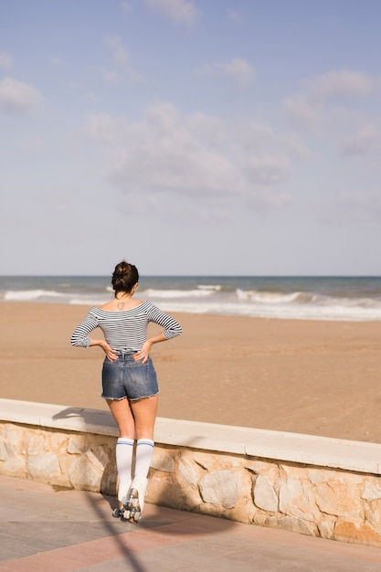 Rear view of a female skater with hand on her hip looking at sea Free Photo