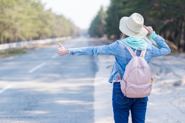 Rear view of a female with hat and backpack hitchhiking at countryside road Free Photo