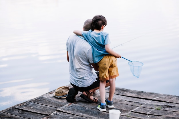 Rear view of a fisherman with his son fishing on lake Free Photo
