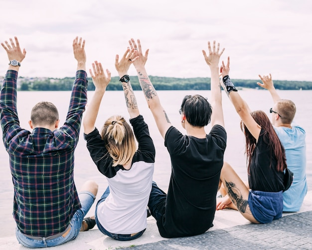 Rear view of friends sitting near the lake raising their hands Free Photo