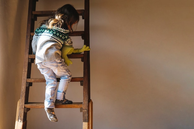 Rear view of a girl climbing ladder Free Photo