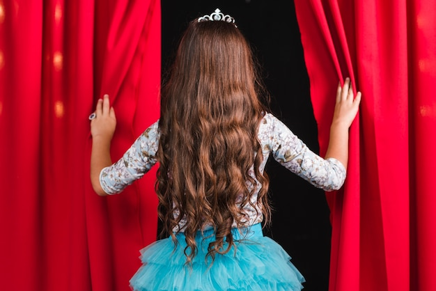 Rear view of girl with long brunette wavy hair looking from red curtain Free Photo