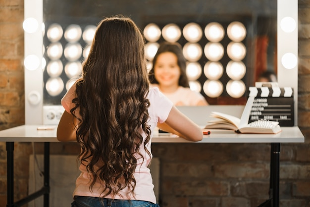 Rear view of girl with long brunette wavy hair sitting in makeup room Free Photo