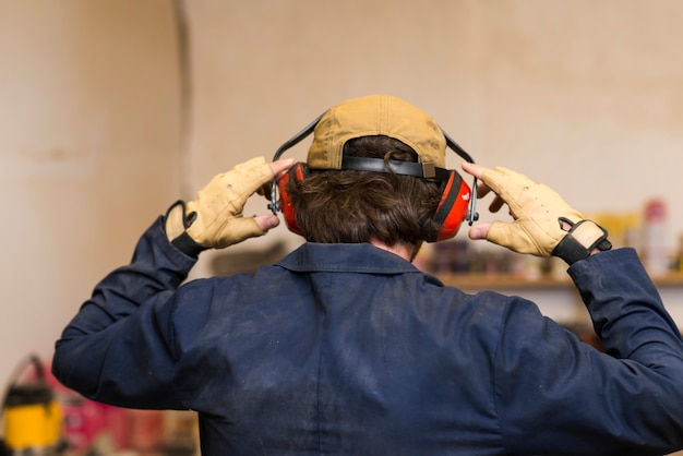 Rear view of a handyman wearing ear defender over his ear Free Photo