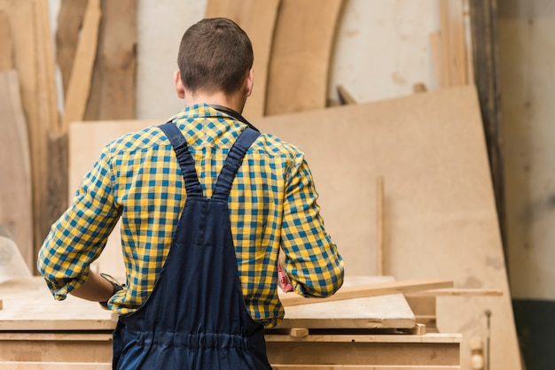 Rear view of a handyman working in the workshop Free Photo