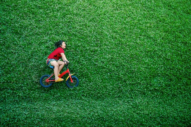 Rear view of a happy asian kids. girl on bicycle lay down at green lawn in summer day Premium Photo