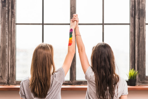 Rear view of lesbian young couple holding each other's hands standing in front of window Free Photo
