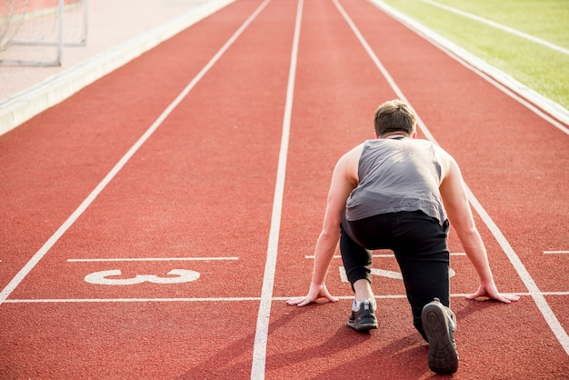 Rear view of male athlete ready to start the relay race on running track Free Photo