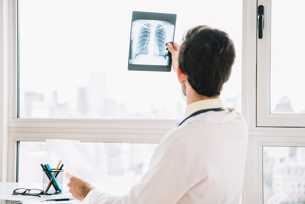 Rear view of a male doctor examining chest x-ray Free Photo