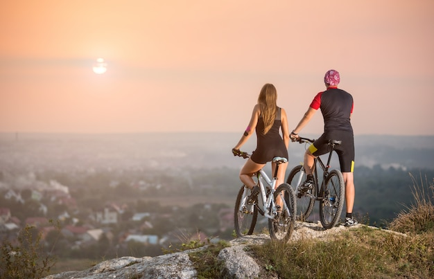 Rear view male and female bikers with moutains bicycles standing on the top of a hill Premium Photo