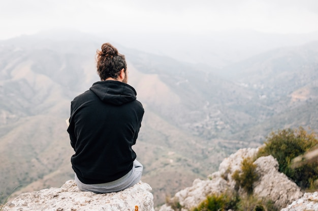 Rear view of a male hiker sitting on top of rock overlooking mountain view Free Photo