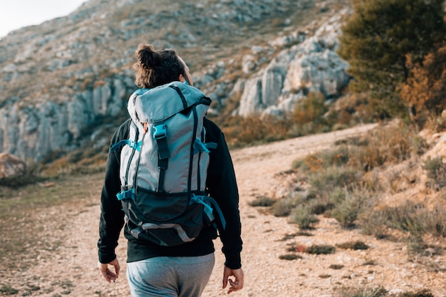 Rear view of a male hiker with backpack hiking in the mountains Free Photo