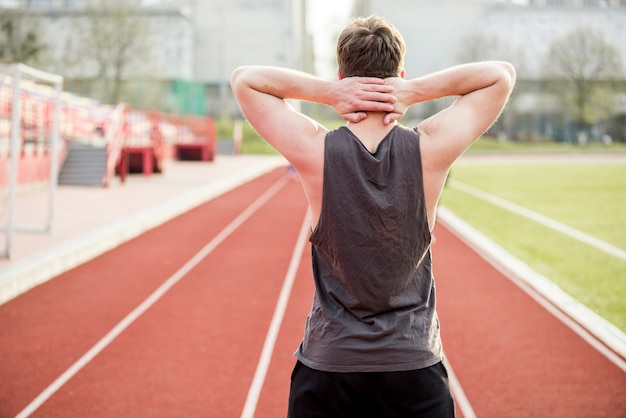 Rear view of a male runner standing on race track with her hands behind his head Free Photo