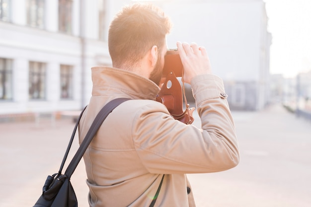 Rear view of a male traveler taking the picture in the city with camera Free Photo