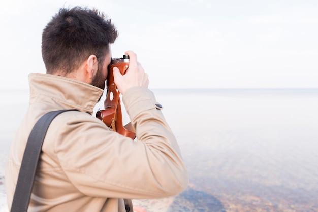Rear view of a male traveler taking picture of idyllic sea with camera Free Photo