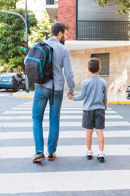 Rear view of a man carrying school bag walking on crosswalk with his son Free Photo