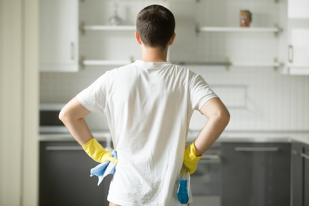 Rear view at man hands at his hips, observing kitchen Free Photo