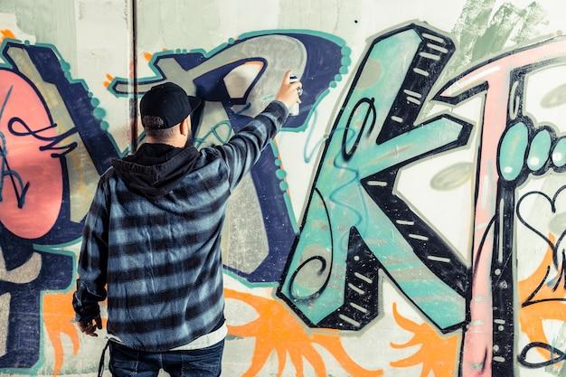 Rear view of a man making graffiti on wall Free Photo