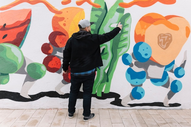 rear view of a man making graffiti with spray can on wall photo