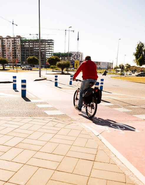 Rear view of a man riding the bicycle on street in the city Free Photo
