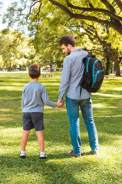 Rear view of a man standing with his son in the park Free Photo