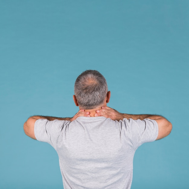 Rear view of man suffering from neck pain over blue backdrop Free Photo