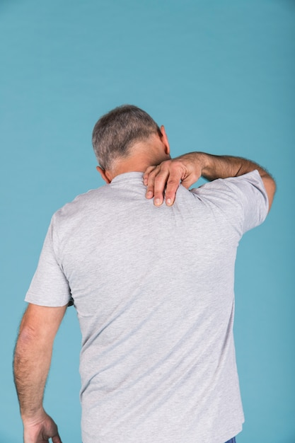 Rear view of a man suffering from neck pain in front of blue backdrop Free Photo