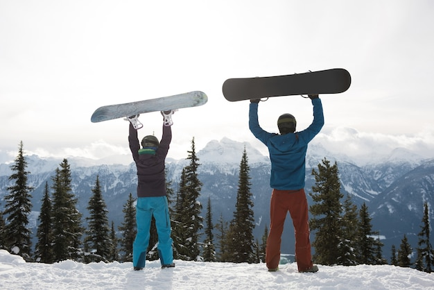 Rear view of man and woman holding snowboard at mountain during winter Free Photo