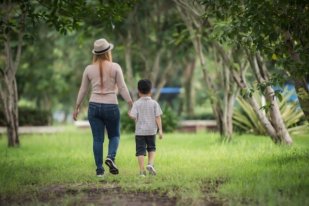 Rear view of mother and son walking together in home garden holding hand. Free Photo