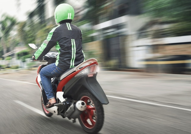 Rear view of motorcycle taxi ride with fast Premium Photo