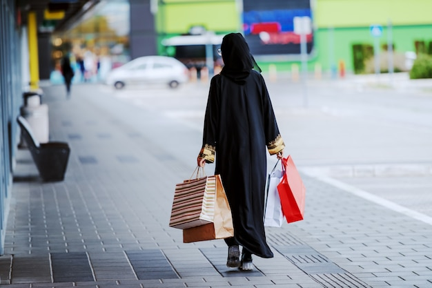 Rear view of muslim woman in traditional wear walking outdoors with shopping bags in hands. fashion is for everyone. diversity concept. Premium Photo