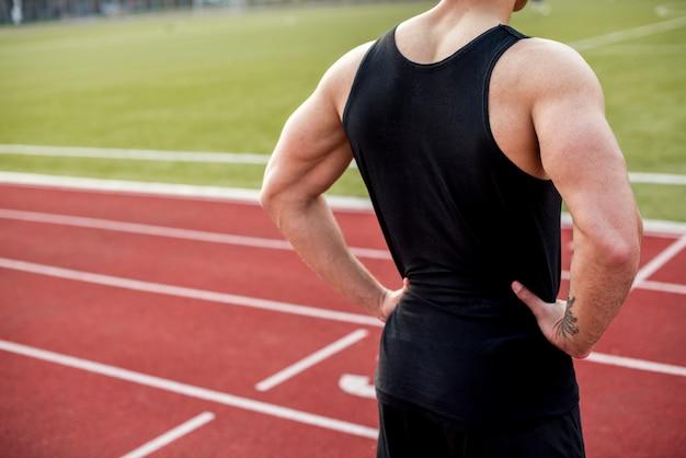 Вид сзади мыжского спортсмена с руки на бедра, стоя на гоночной трассе Бесплатные Фотографии