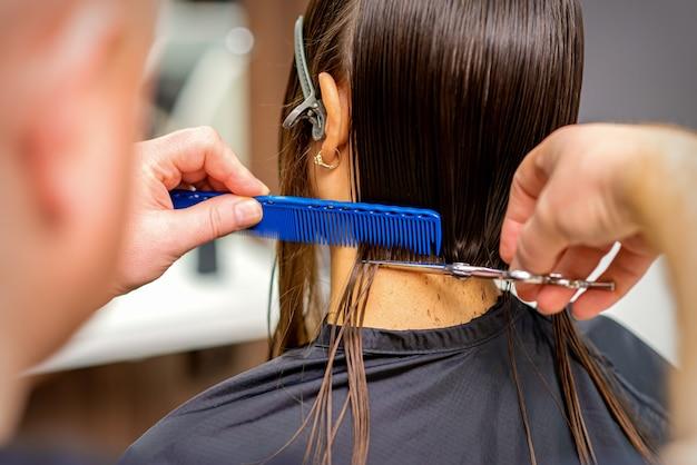 남성 미용사의 뒷모습은 Siscors와 빗으로 젊은 여성의 머리카락을 자릅니다. 프리미엄 사진