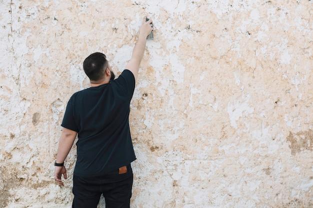 Вид сзади человека, делающего граффити на очищенной стене Бесплатные Фотографии