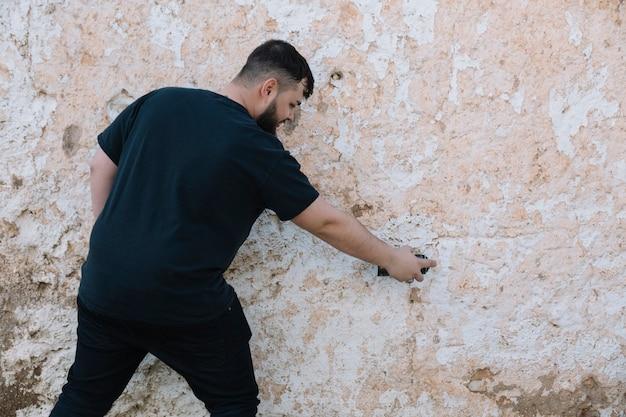 Вид сзади человека, рисующего граффити на поврежденной стене Бесплатные Фотографии