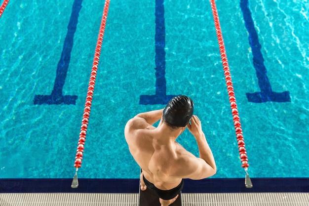 水泳ゴーグルを準備する男の後姿 無料写真