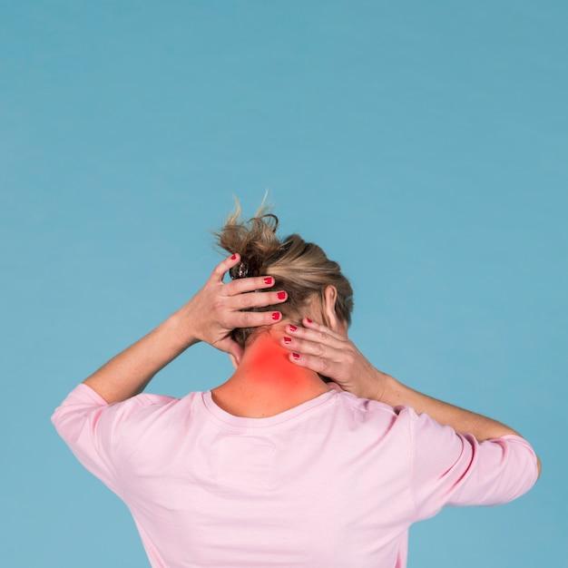 Вид сзади женщины страдают от боли в шее на синем фоне Premium Фотографии